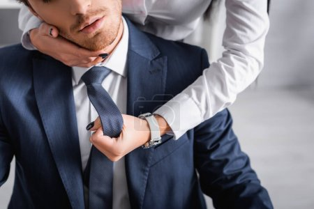 Photo for Partial view of secretary flirting with businessman and touching his face in office - Royalty Free Image