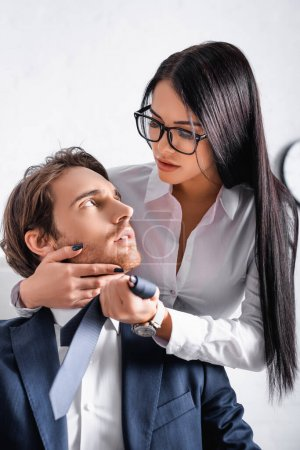 Photo for Sensual brunette businesswoman touching face of colleague while seducing him in office - Royalty Free Image