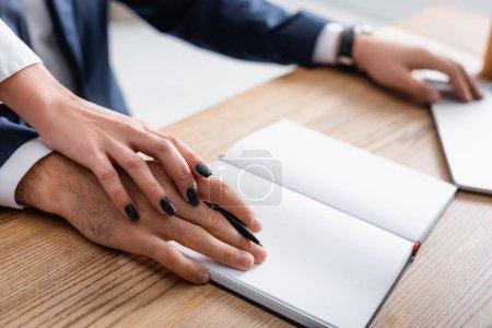 abgeschnittene Ansicht der Geschäftsfrau, die Hand eines Kollegen in der Nähe eines leeren Notizbuchs auf dem Schreibtisch berührt, verschwommener Hintergrund