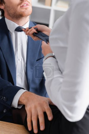 cropped view of passionate businesswoman pulling tie of businessman while seducing him in office, blurred foreground