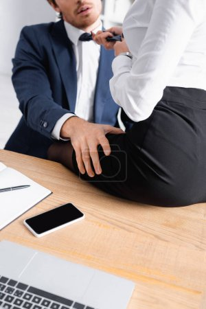 cropped view of businesswoman sitting on desk while seducing colleague in office