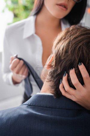 abgeschnittene Ansicht der verführerischen Sekretärin, die Krawatte zieht und den Kopf des Geschäftsmannes im Büro berührt, verschwommener Hintergrund