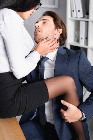 Photo pour Homme d'affaires passionné étreignant jambe de femme d'affaires assis sur le bureau et touchant son visage - image libre de droit