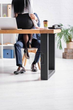 Photo pour Vue recadrée de femme d'affaires assise sur le bureau tout en séduisant collègue au bureau - image libre de droit