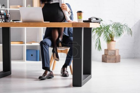 partial view of secretary sitting on desk near laptop and seducing colleague in office