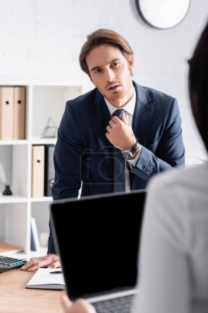 young businessman adjusting tie while looking at secretary with laptop on blurred foreground