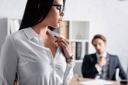 Photo for Passionate brunette businesswoman touching blouse while seducing colleague on blurred background - Royalty Free Image