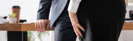 Teilansicht von Sekretärin nahe Geschäftsmann auf verschwommenem Hintergrund, Banner