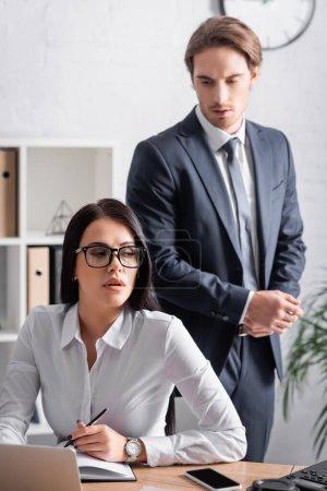 businessman near seductive brunette secretary sitting at workplace with pen