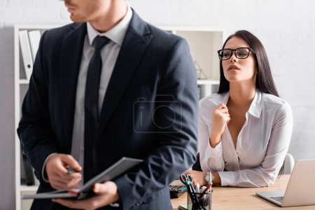 seductive businesswoman at workplace looking at colleague holding notebook on blurred foreground