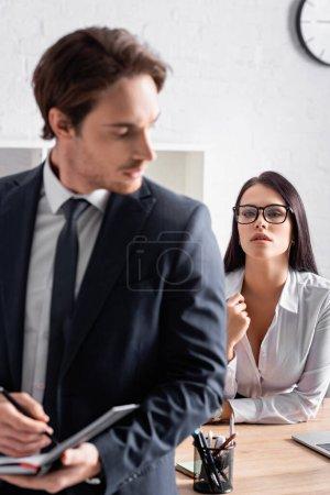Leidenschaftliche Sekretärin mit Brille verführt Geschäftsmann auf verschwommenem Vordergrund