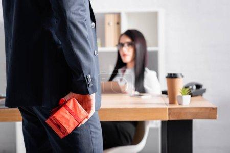 businessman holding gift box near brunette secretary on blurred background