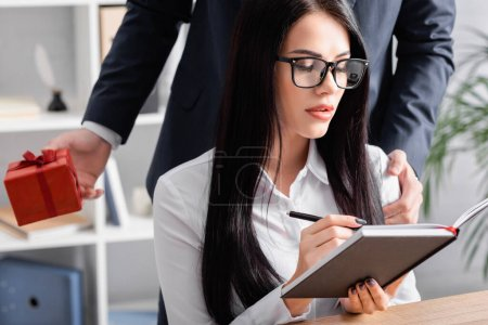 businessman touching shoulder of sexy secretary while holding valentines day gift