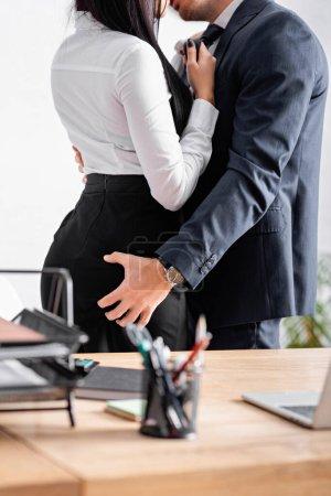 Teilbild eines Geschäftsmannes, der Geschäftsfrau im Büro umarmt und küsst