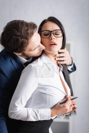 leidenschaftliche Geschäftsfrau knöpft Bluse auf, während junge Kollegin sie im Büro verführt