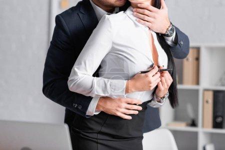 vue recadrée de secrétaire déboutonner chemisier tandis que l'homme d'affaires l'embrasser dans le bureau