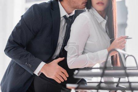 Teilansicht des Geschäftsmannes, der die Hüfte der verführerischen Geschäftsfrau im Amt umarmt, verschwommener Vordergrund