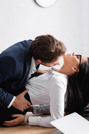 junger Geschäftsmann küsst leidenschaftliche brünette Geschäftsfrau auf Schreibtisch im Büro