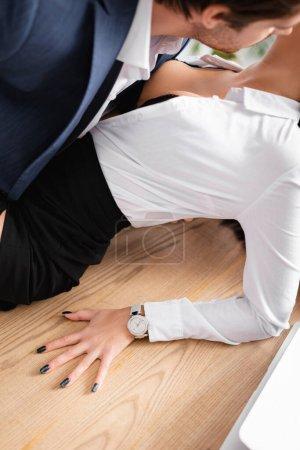 Teilansicht von Geschäftsfrau nahe verführerischer Geschäftsfrau auf Schreibtisch im Büro