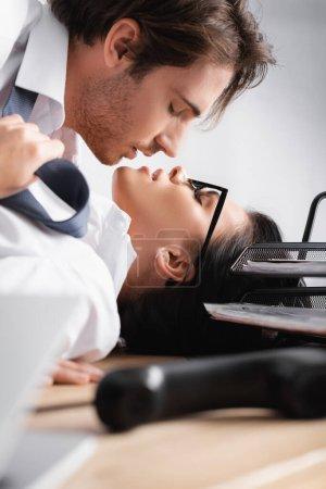 Photo pour Vue de côté de l'homme d'affaires embrasser secrétaire sensuelle près combiné sur le premier plan flou - image libre de droit