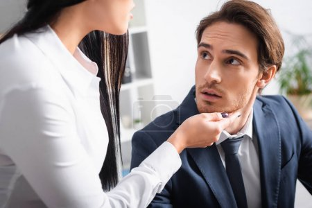 verführerische Geschäftsfrau berührt Kinn einer jungen Kollegin im Amt