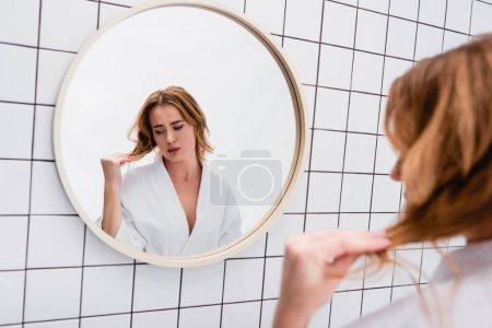worried woman in bathrobe looking at hair in bathroom