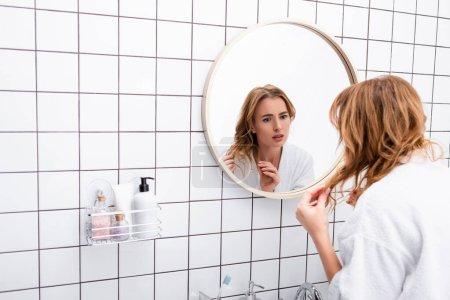 worried woman in bathrobe adjusting hair while looking at mirror in bathroom