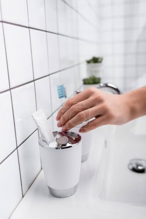 cropped view of woman taking toothbrush in bathroom