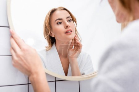woman looking at mirror and touching face in bathroom