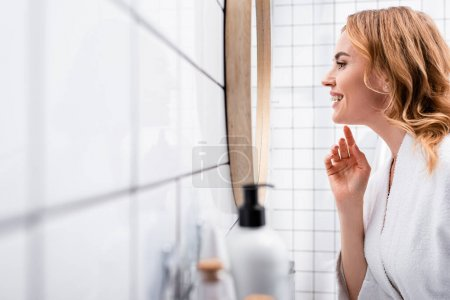 Photo for Side view of happy woman looking at mirror near bottles on blurred foreground - Royalty Free Image