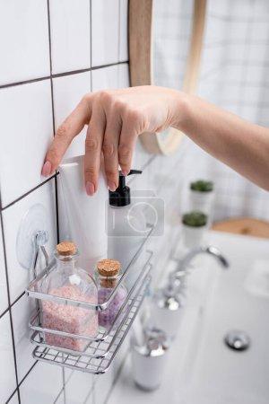 Photo pour Vue recadrée de la femme prenant tube avec des produits cosmétiques près des bouteilles avec du sel de mer - image libre de droit