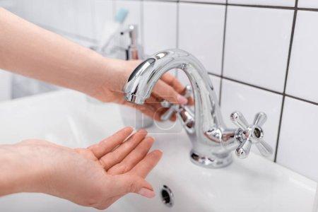vista recortada del grifo de apertura de mujer en el baño
