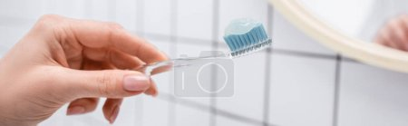 cropped view of woman holding toothbrush with toothpaste in hand, banner