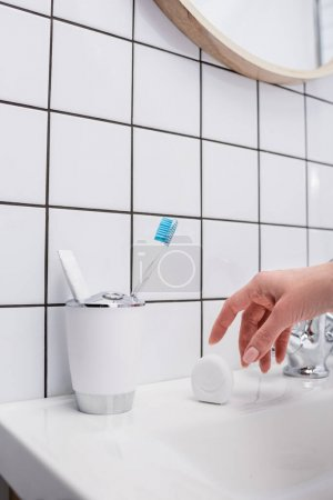 cropped view of woman reaching container with dental floss in bathroom