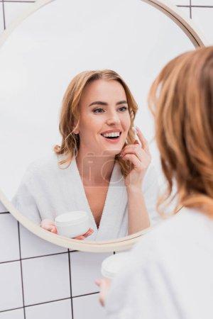 femme heureuse tenant pot et appliquer de la crème visage tout en regardant miroir