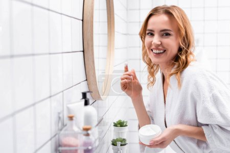 smiling woman holding jar with face cream near mirror near bottles on blurred foreground