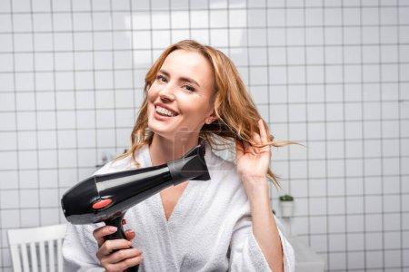 Photo pour Femme gaie en peignoir blanc séchage cheveux brillants dans la salle de bain - image libre de droit