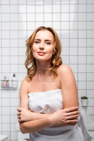 woman in wrapped in white towel standing and looking at camera in bathroom