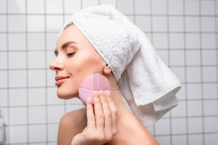 Photo for Pleased woman in towel on head using cleansing silicone brush in bathroom - Royalty Free Image