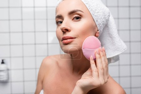 woman in towel on head using cleansing silicone brush in bathroom