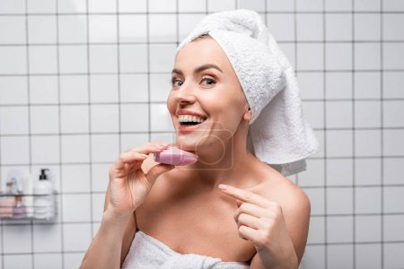 cheerful woman in towel on head pointing with finger at cleansing silicone brush in bathroom