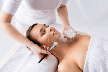 esteticista celebración de cepillo cosmético y contenedor con mascarilla cerca del cliente con los ojos cerrados acostado en la mesa de masaje