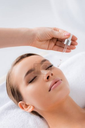beautician holding pipette and applying serum on face of client in spa salon