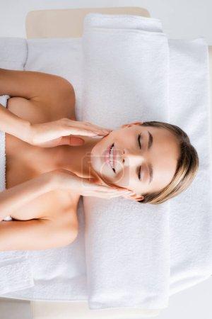 vista superior de la mujer feliz tocando las mejillas y acostado en la mesa de masaje en el salón de spa