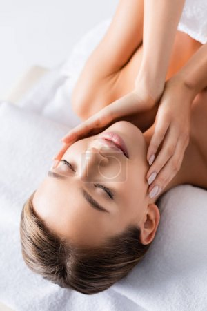 pleased young woman with closed eyes touching face and lying on massage table in spa salon