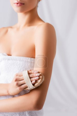 partial view of young woman exfoliating skin with brush on white
