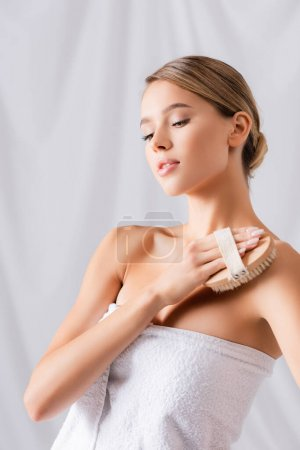 attractive young woman exfoliating skin with brush on white