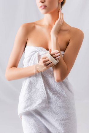 partial view of young woman wrapped in towel exfoliating skin with brush on white