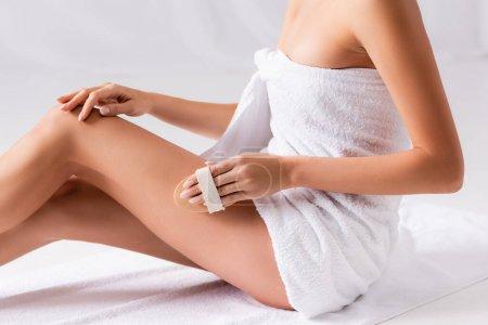 vue recadrée de la femme enveloppée dans une serviette massante jambe avec brosse sur blanc