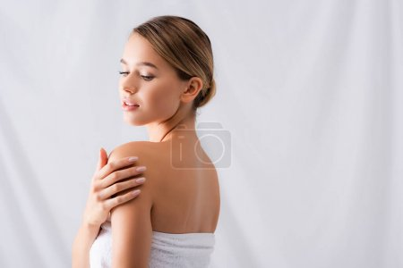 young woman touching bare shoulders on white
